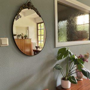 Antieke ovale spiegel met versiering aan bovenkant